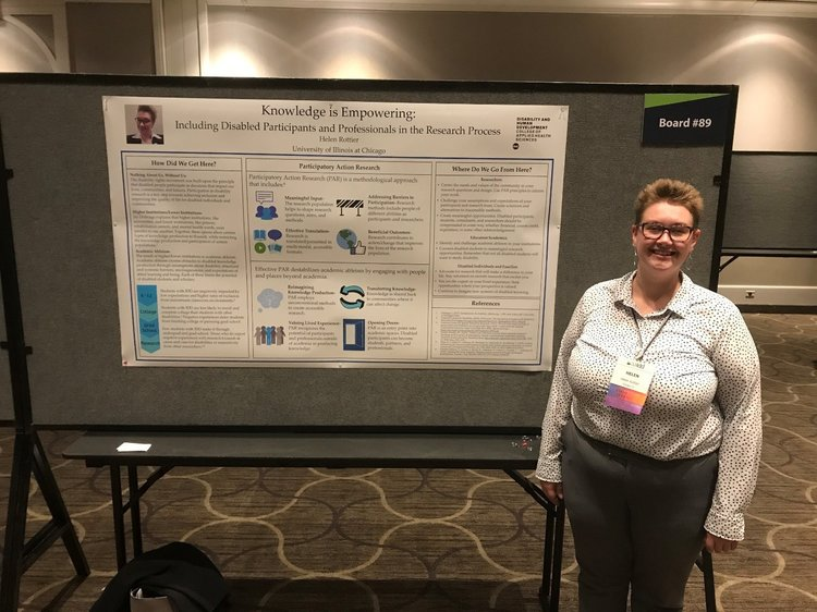 image of Helen, a young white woman with short blonde hair and rainbow glasses. Helen is wearing a white collared shirt, grey dress pants, a conference name tag, rainbow glasses, and silver earrings. She is standing in front of a poster on including disabled people in research.