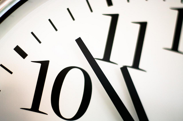 close up of a clock face with the numbers 10 and 11 and two clock hands visible